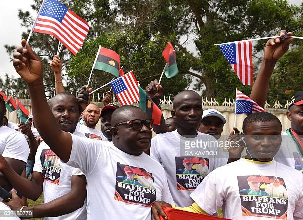 Graphic content / Biafrans wave the US flag and the former Republic of Biafra rally outside the American Embassy in Abidjan on January 20 as...