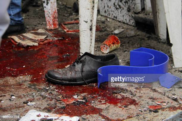 Graphic content / Blood and debris are seen on a street near a church in Alexandria after a bomb blast struck worshippers gathering to celebrate Palm...