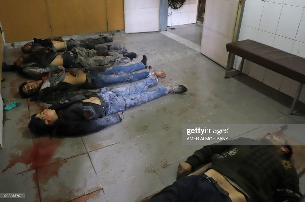Graphic content / Bodies are lined up on the floor at a make-shift hospital in Kafr Batna in the besieged Eastern Ghouta region on the outskirts of the capital Damascus following Syrian government bombardments on February 21, 2018. Syrian jets carried out more deadly raids on Eastern Ghouta as Western powers and aid agencies voiced alarm over the mounting death toll and spiralling humanitarian catastrophe. PHOTO / Amer ALMOHIBANY