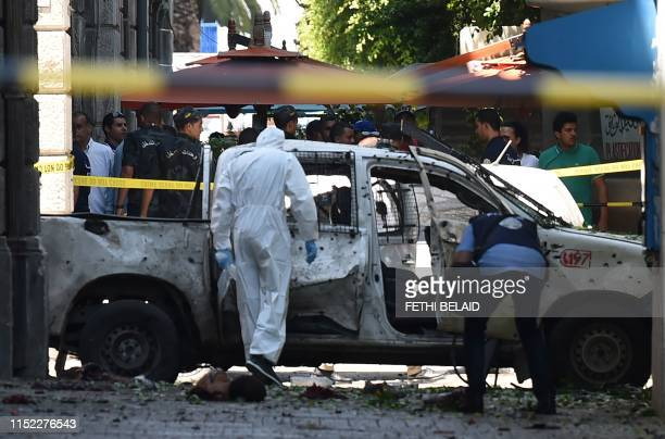 Graphic content / Body parts lie next to a shrapnel riddled vehicle as Tunisian forensic work at the site of attack in the Tunisian capital's main...