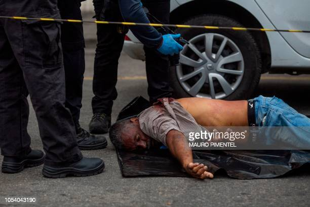 Graphic content / Brazilian investigative police officers work at the crime scene where a man was found shot dead inside a car, in front of the Law...