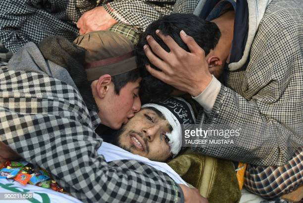 Graphic content / Brothers of the 16 year old Kashmiri rebel Fardeen Ahmad Khandey mourn during a funeral procession in Tral area of South Kashmir on...