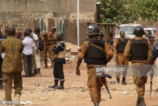 Graphic content / Burkina Faso security force personnel stand with an injured colleague in Ouagadougou on May 22 after a predawn raid by security...