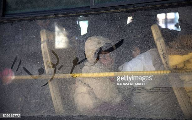 Graphic content / Children are seen inside a bus with words in Arabic reading 'some day we will return' written on the window during an evacuation...