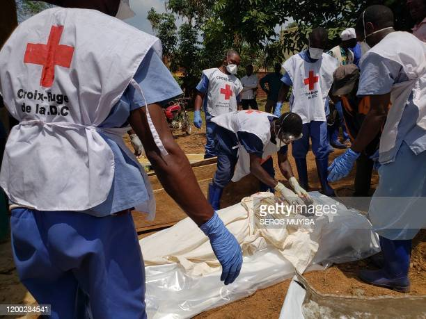 Graphic content / Democratic Republic of Congo's Red Cross members wearing gloves and masks handling dead bodies in Mangina on February 10 that were...