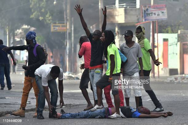 Graphic content / Demonstrators gesture next to the body of a dead protester during clashes with Haitian Police in the center of Haitian capital...