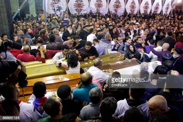 Graphic content / Egyptian Christians gather around and mourn by coffins during the late night funeral of the victims of a blast which killed...