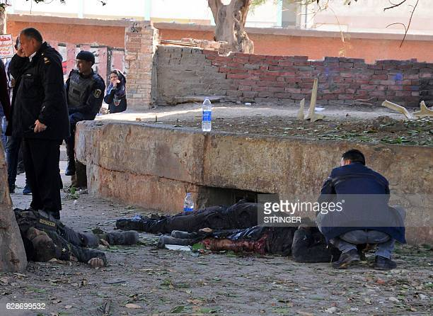 Graphic content / Egyptians check bodies at the site of a bomb attack next to a police checkpoint in the western Talibiya district of the capital...