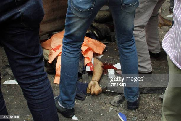 Graphic content / Egyptians gather around a body in a street near a church in Alexandria after a bomb blast struck worshippers gathering to celebrate...