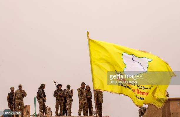 Graphic content / Fighters of the Syrian Democratic Forces stand atop a roof next to their unfurled flag at a position in the village of Baghouz in...