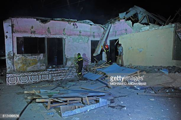 Graphic content / Firefighters try to secure a building after an attack in the center of Mogadishu on February 26 2016 At least 12 people were killed...