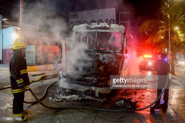 Graphic content / Firefighters work after a bus was set on fire in Acapulco Guerrero State Mexico on November 22 2019 AFP has mobilized several of...