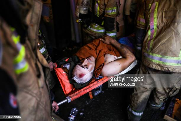 Graphic content / First responders carry away an injured person on a stretcher at the scene of an explosion at the Sina At'har health centre in the...