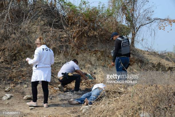 Graphic content / Forensic experts, investigators of the prosecution office and policemen work at the crime scene next to a man's corpse in Acapulco,...