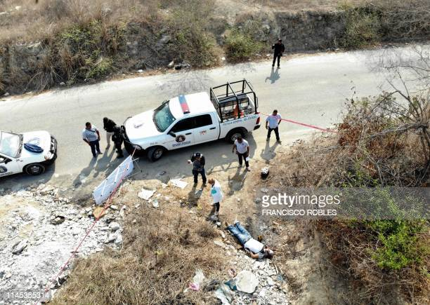 Graphic content / Forensic experts investigators of the prosecution office and policemen work at the crime scene next to a man's corpse in Acapulco...