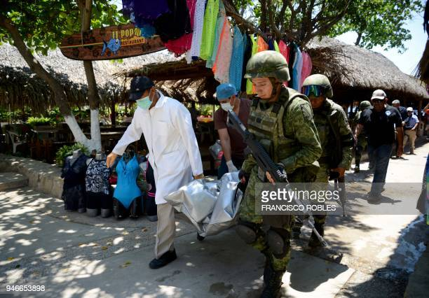 Graphic content / Forensic personnel and Mexican soldiers carry the corpse of a murdered man who was found in Caletilla Beach Acapulco Guerrero state...