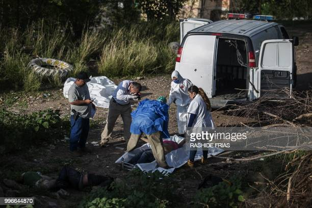 Graphic content / Forensic personnel inspect the bodies of three people found murdered in Culiacan Sinaloa State Mexico on July 11 2018