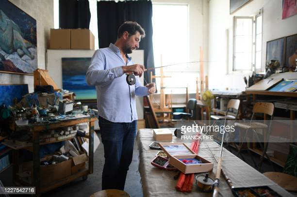 Graphic content / French artist Olivier Masmonteil, initiator of the project, sets up a fishing rod with a fly fishing kit in the colours of the...