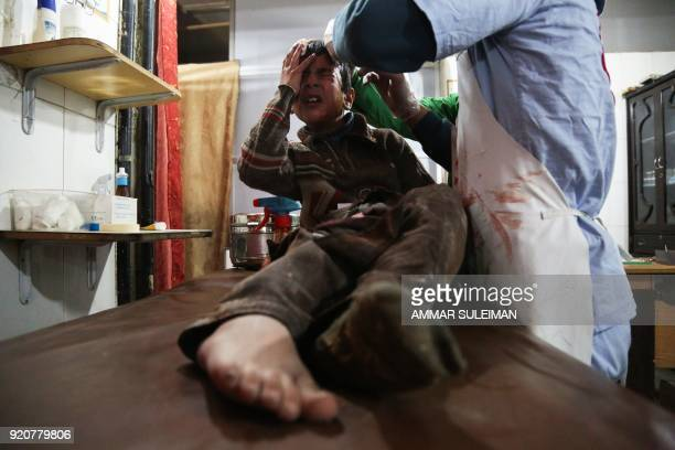 Graphic content / Ghaith a wounded 12yearold Syrian boy cries as he receives treatment at a makeshift hospital in Kafr Batna and waits for news of...