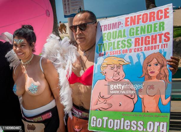 Graphic content / GoTopless Day demonstrators hold a sign featuring the US president and his wife as they march during their annual protest for...