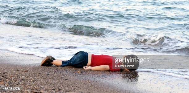 Graphic content / GRAPHIC CONTENT A migrant child's dead body lies on the shores in Bodrum, southern Turkey, on September 2, 2015 after a boat...