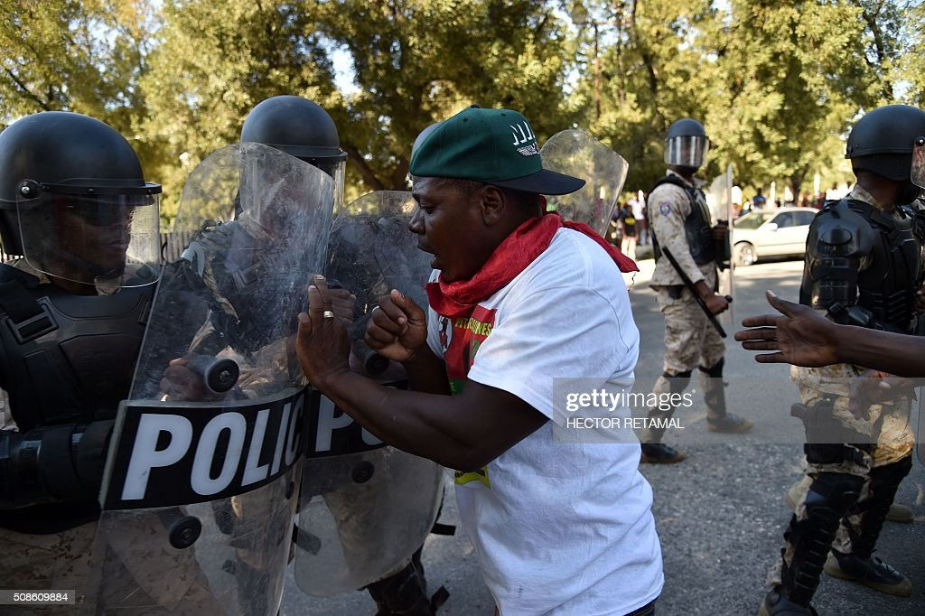 Graphic content / Haitian policemen confront demonstrators during a protest agaist President Michel Martelly and for a transitional government in Port-au-Prince on February 5, 2016. President Michel Martelly's term ends February 7, and with no successor in place, Haiti is facing constitutional crisis. Haiti's electoral authority postponed the planned January 24 presidential run-off amid mounting opposition street protests and voting fraud allegations. / AFP / HECTOR