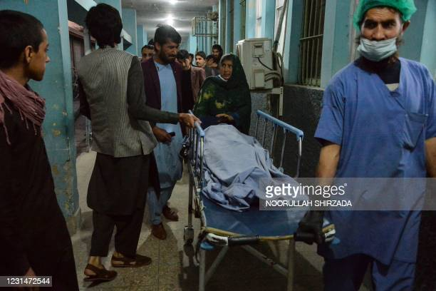 Graphic content / Hospital workers and relatives shift the body of one of the three female media workers shot to death in two separate attacks, at a...