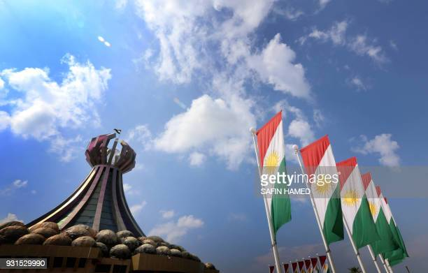 Graphic content / In this file photo taken on March 16, 2014 the Kurdish flags flutter close to a monument for the Iraqi Kurd victims who were killed...