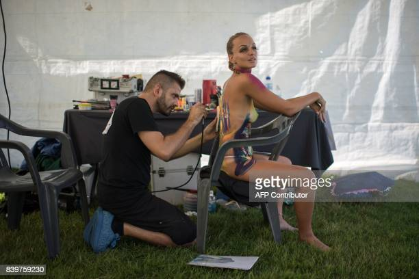 Graphic content / In this photo taken on August 26 contestant Emanuele Borello of Italy applies his designs to a model during the Daegu International...