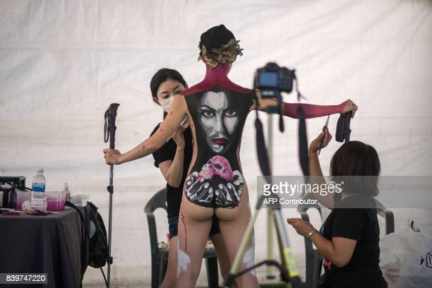 Graphic content / In this photo taken on August 26 contestants apply their designs to a model during the Daegu International Bodypainting Festival in...