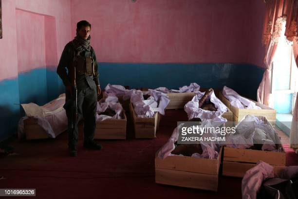 Graphic content / In this photograph taken on August 14 Afghan policeman stands next to the coffins containing corpses following clashes with Taliban...