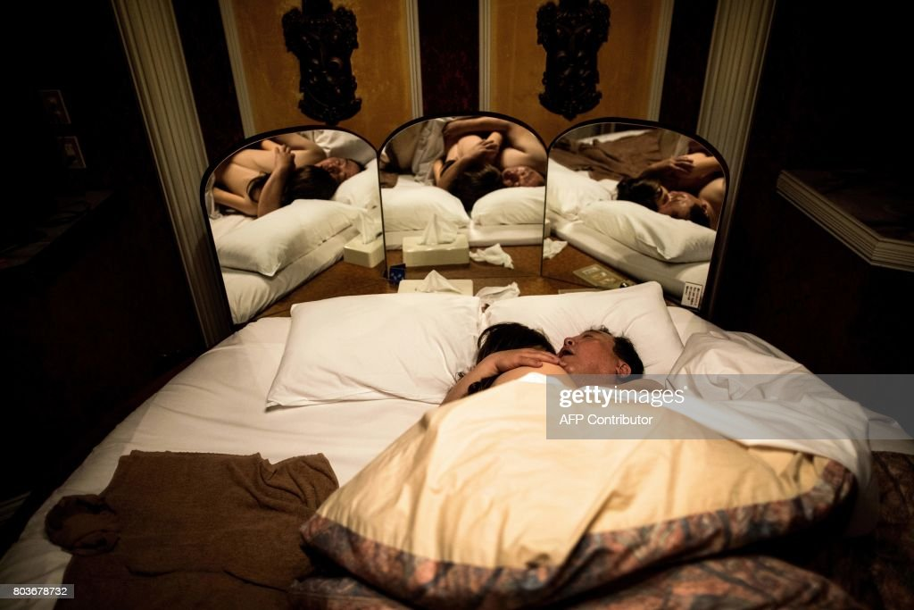 Graphic content / In this picture taken early on June 14, 2017, 62-year-old Senji Nakajima hugs his silicone sex doll Saori while sleeping at a love hotel in Yachimata, Chiba prefecture. Around 2,000 of the life-like dolls -- which cost around 6,000 USD and come with adjustable fingers, removable head and life-like genitals -- are sold each year in Japan, according to industry insiders. / AFP PHOTO / Behrouz MEHRI / TO GO WITH Japan-social-lifestyle,FEATURE by Alastair HIMMER