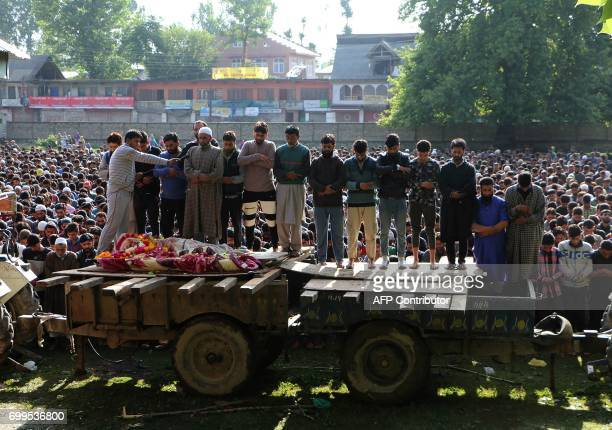 Graphic content / Indian Kashmiri villagers offer prayers for a Kashmiri rebel over his body during a funeral procession in Pulwama south of Srinagar...