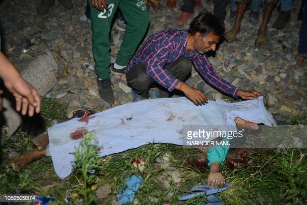 Graphic content / Indian Mukesh Kumar looks at dead body of his son Neeraj Kumar who was killed in a train accident as he was participating in the...