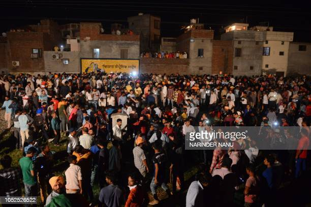 Graphic content / Indian relatives and revellers gather around the bodies of the victims of a train accident during the occasion of the Hindu...