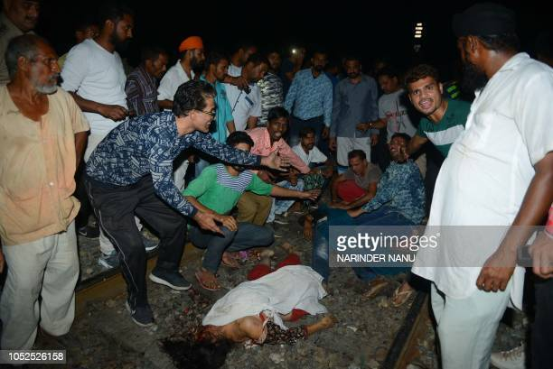 Graphic content / Indian relatives and revellers look at bodies of the victims of a train accident during the occasion of the Hindu festival of...