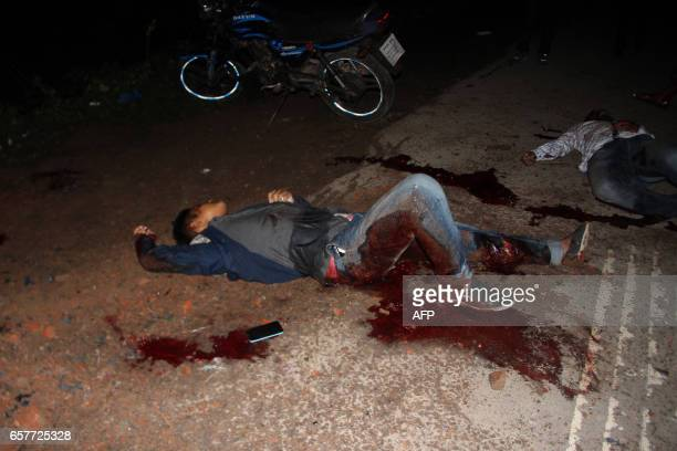 Graphic content / Injured Bangladeshi security personel lie on ground after a blast near an Islamist extremist hideout raided by army in Sylhet on...