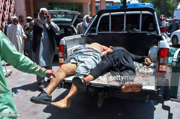 Graphic content / Injured men are transported on a truck to a hospital following a suicide attack at a funeral of a local police commander in...