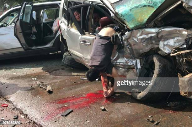 Graphic content / Injured passengers are seen in the damaged vehicle beside the car of Cambodian Prince Norodom Ranariddh and his wife Ouk Phalla...