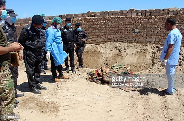 Graphic content / Iraqi forensics look at a body after they dug it out of what is believed to be a mass grave in the central Iraqi city of Ramadi on...