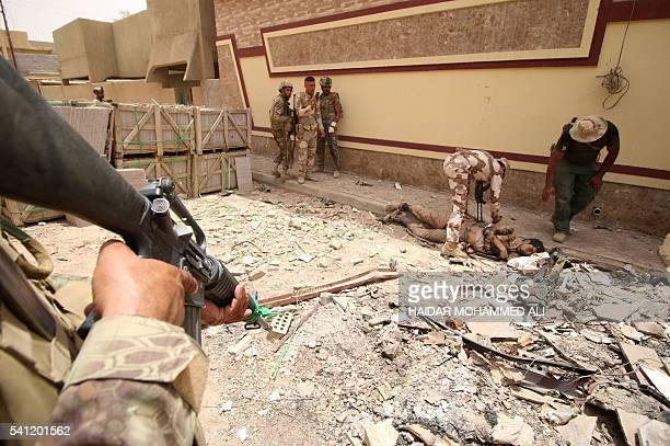 Graphic content / Iraqi progovernment forces check an unidentified body as they patrol the alDhubat II neighbourhood of Fallujah as they try to clear...