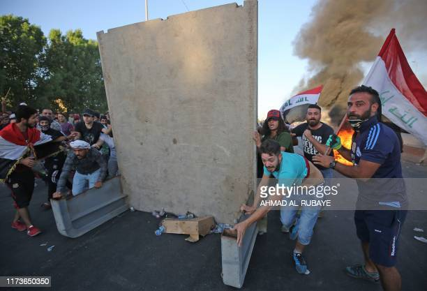 Graphic content / Iraqi protesters take cover during a demonstration against state corruption failing public services and unemployment in the Iraqi...