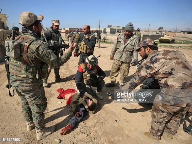Graphic content / Iraqi security forces evacuate a comrade gravely wounded in an explosivesladen vehicle attack claimed by Islamic State group as the...