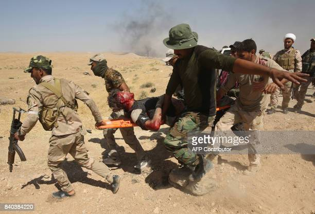 Graphic content / Iraqi soldiers carry a wounded comrade as they advance towrds the village of alAyadieh near Qubuq north of Tal Afar during the...