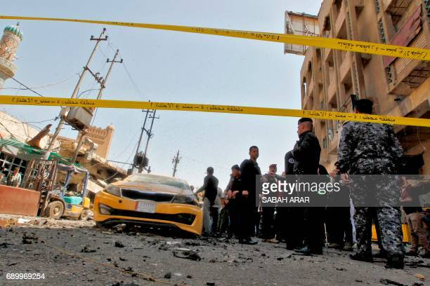 Graphic content / Iraqis gather at the site of a car bomb explosion near Baghdad's Al-Shuhada Bridge on May 30, 2017 which killed at least five...