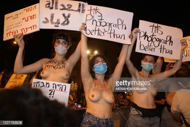 Graphic content / Israeli activists hold placards against the killing of Iyad Hallak, a 32-year-old autistic Palestinian man shot dead by Israeli...
