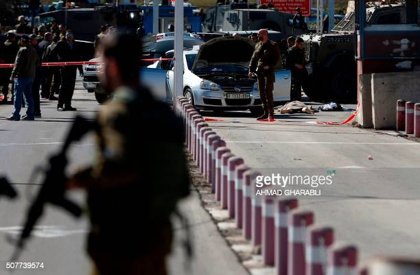 Graphic content / Israeli security forces gather around the body of a Palestinian man who was shot dead following a reported shooting attack on...