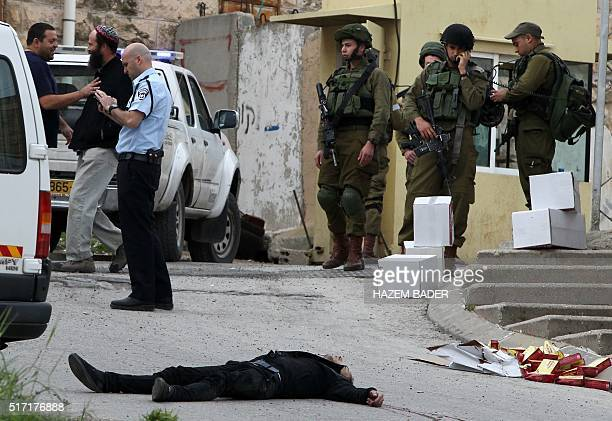 Graphic content / Israeli soldiers and police surround the body of one of two Palestinians who were killed after wounding an Israeli soldier in a...