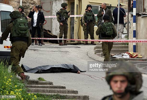 Graphic content / Israeli soliders surround the body of one of the two Palestinians who were killed after wounding an Israeli soldier in a knife...