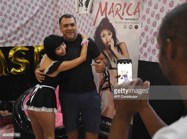 Graphic content / Japanese porn star Marica poses with a fan during the annual 'AdultCon' Adult Entertainment Convention in Los Angeles California on...